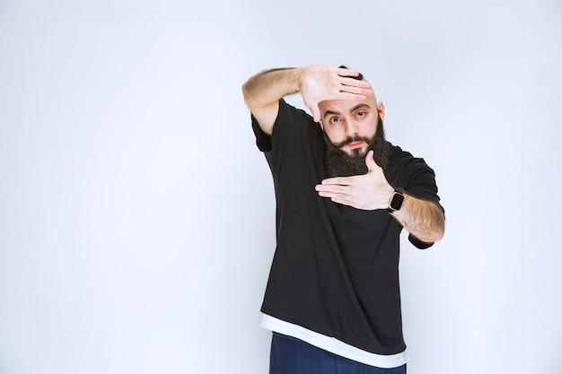 写真撮影のサインを示すひげを持つ男。