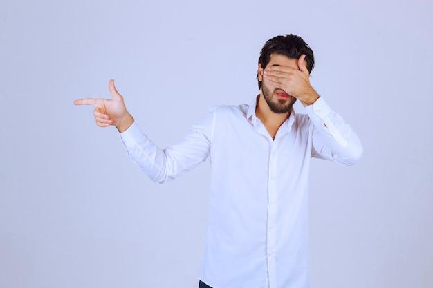 Человек с бородой показывает палец вверх по знаку.