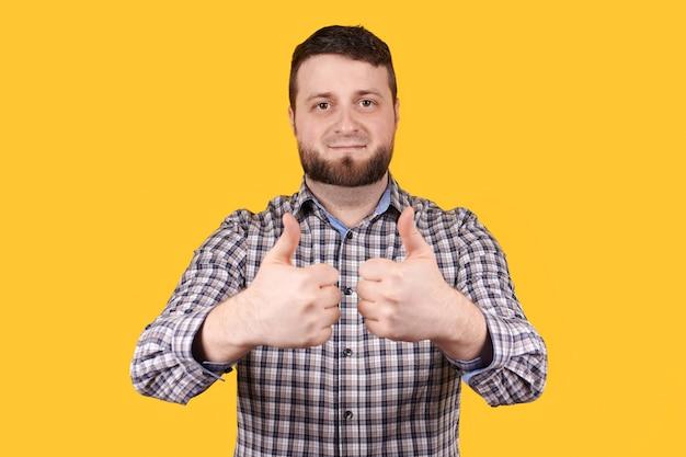 ひげを持つ男は承認のために親指を表示し、オレンジ色のスペースで分離されました。
