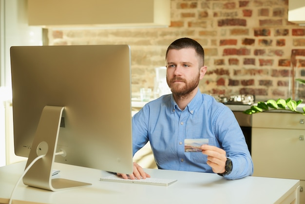A man with a beard sits in front of the computer and types a credit card information on an online store at home