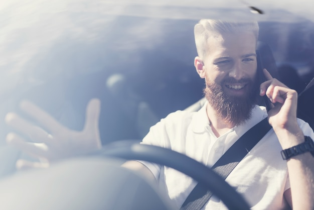Man with a beard sits at the wheel of an electric vehicle