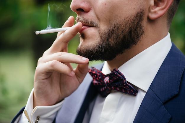 Man with beard smokes a cigarette