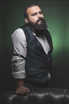 Man with a beard smoking a cigar, looking at the camera.