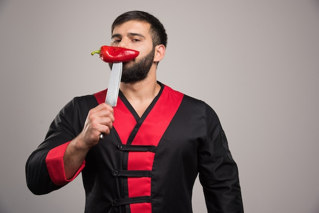 Man with beard sniffs a red pepper on knife.
