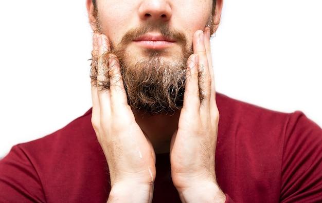 あごひげをリフレッシュするためのあごひげ石鹸またはシャンプーを持つ男
