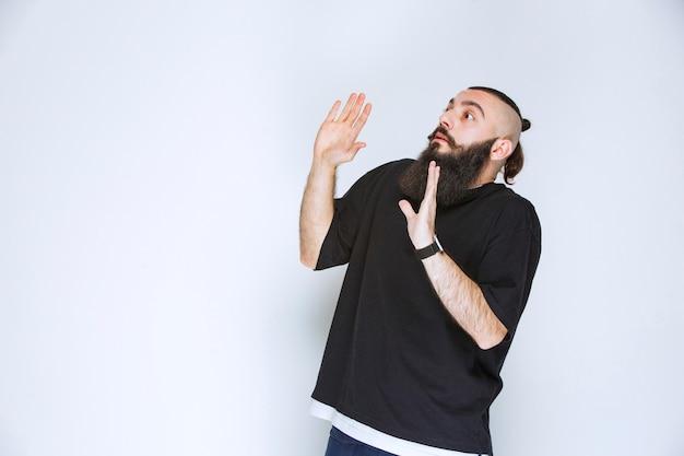 開いた手で何かを停止するひげを持つ男。