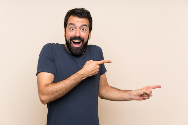 Man with beard surprised and pointing side