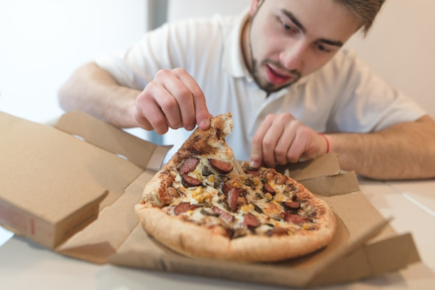 A man with a beard takes a delicious piece of pizza from a cardboard box and looks at her with an appetite.