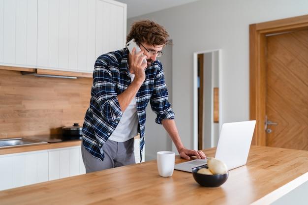 Человек с бородой разговаривает по телефону и использует ноутбук на кухне.