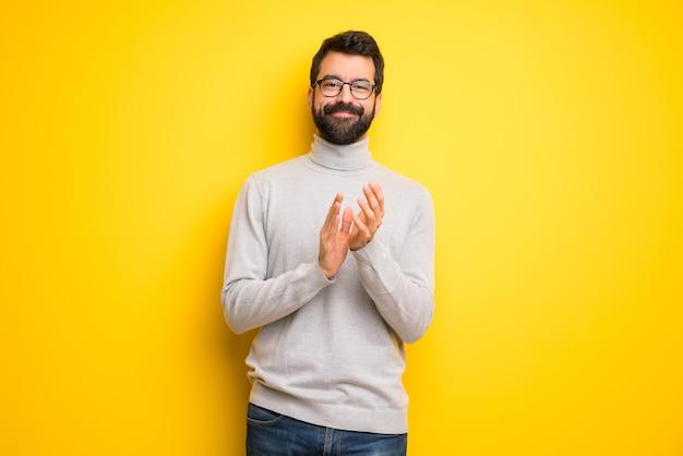 Man with beard and turtleneck applauding after presentation in a conference