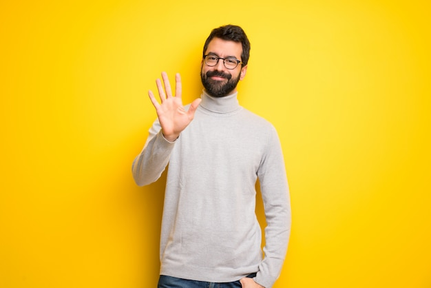 Man with beard and turtleneck counting five with fingers