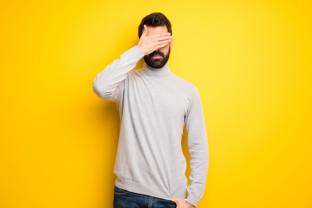 Man with beard and turtleneck covering eyes by hands. do not want to see something