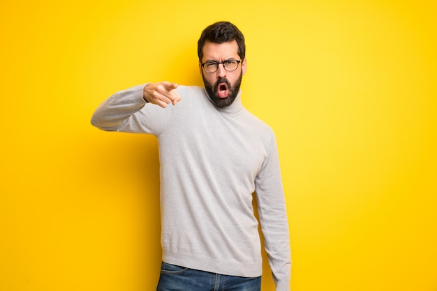 Man with beard and turtleneck frustrated by a bad situation and pointing to the front