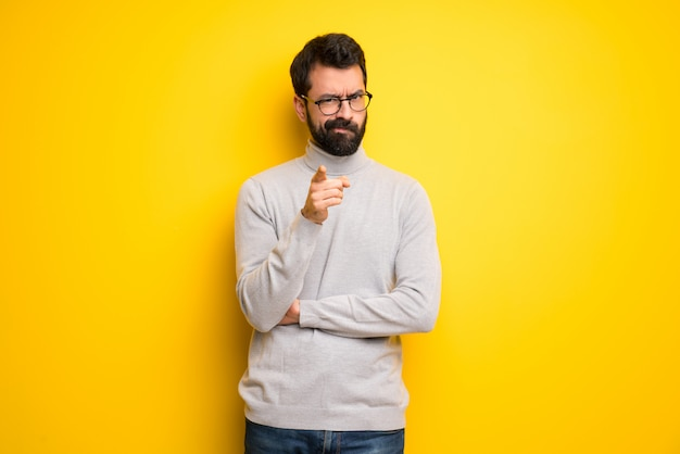 Man with beard and turtleneck frustrated and pointing to the front