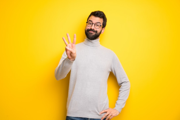 Man with beard and turtleneck happy and counting three with fingers