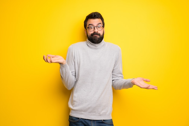 Man with beard and turtleneck having doubts while raising hands and shoulders