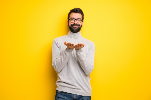 Man with beard and turtleneck holding copyspace imaginary on the palm to insert an ad