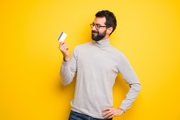 Man with beard and turtleneck holding a credit card and thinking