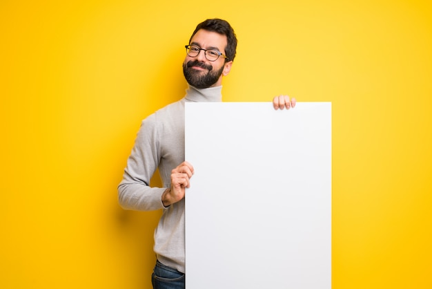 Man with beard and turtleneck holding an empty placard for insert a concept