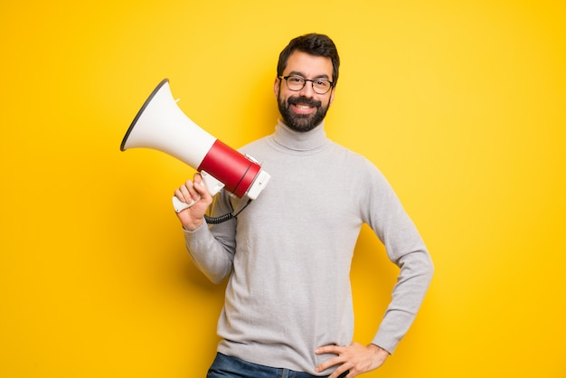 Man with beard and turtleneck holding a megaphone