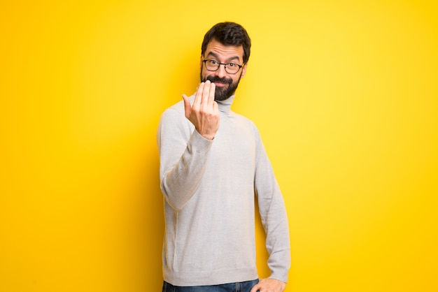 Man with beard and turtleneck inviting to come with hand. happy that you came