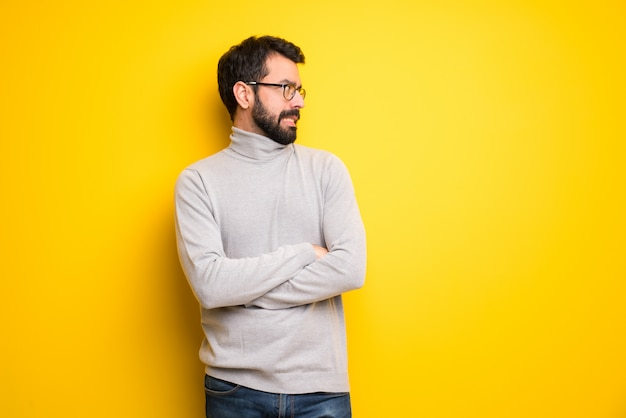 Man with beard and turtleneck is a little bit nervous and scared pressing the teeth