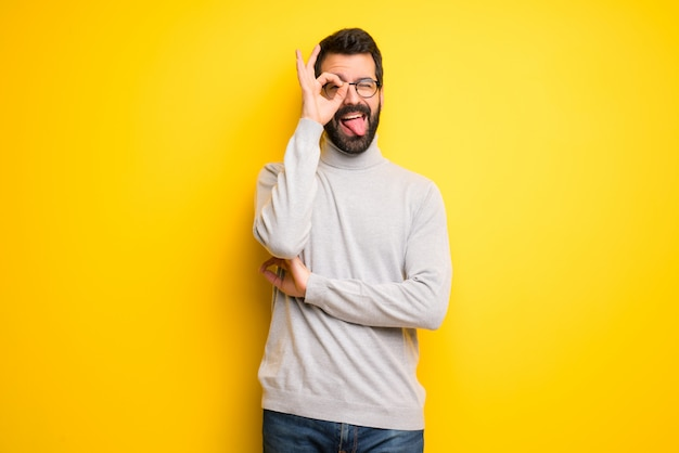 Man with beard and turtleneck makes funny and crazy face emotion