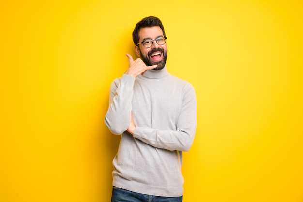 Man with beard and turtleneck making phone gesture. call me back sign