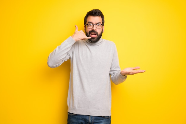 Man with beard and turtleneck making phone gesture and doubting