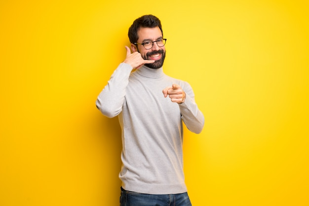 Man with beard and turtleneck making phone gesture and pointing front