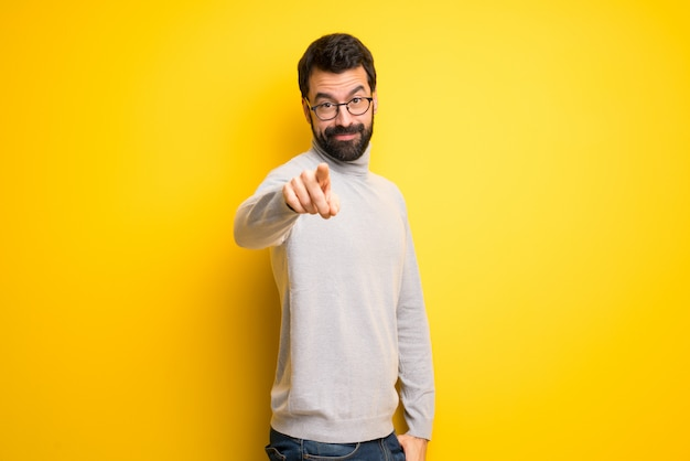 Man with beard and turtleneck points finger at you with a confident expression