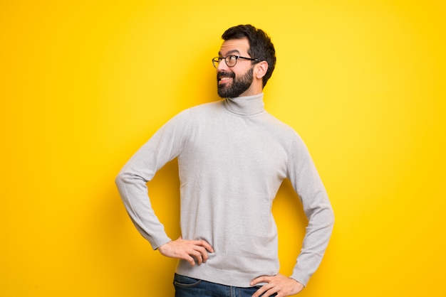 Man with beard and turtleneck posing with arms at hip and laughing