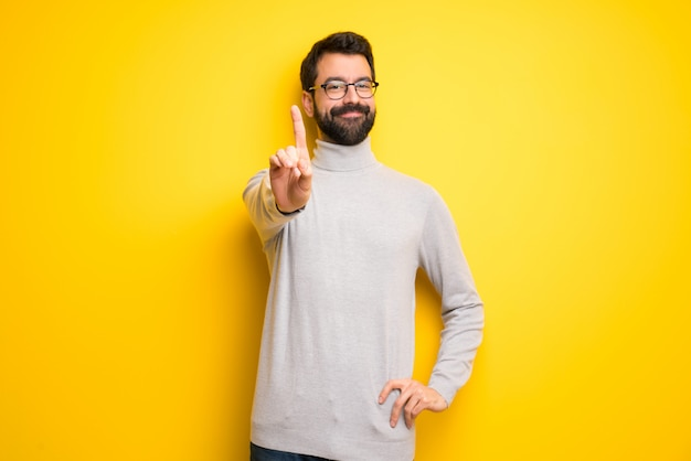 Man with beard and turtleneck showing and lifting a finger