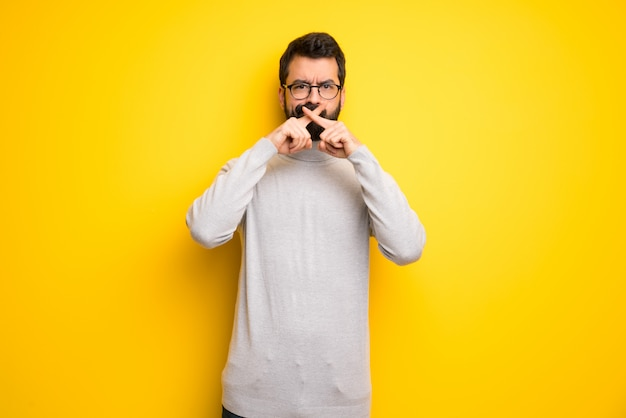 Man with beard and turtleneck showing a sign of silence gesture