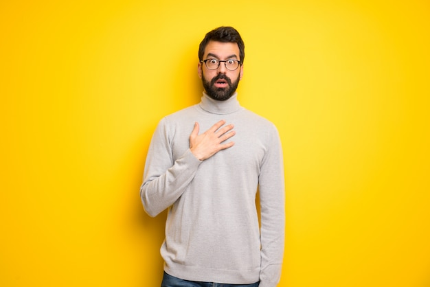 Man with beard and turtleneck surprised and shocked while looking right