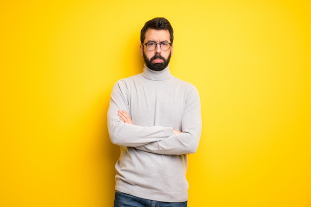 Man with beard and turtleneck with sad and depressed expression