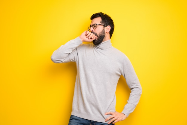 Man with beard and turtleneck yawning and covering wide open mouth with hand