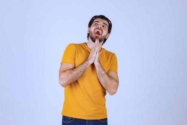 あごひげを生やして手を合わせ、祈って何かを求めている男