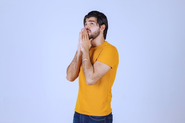 Man with beard uniting his hands and praying and asking for something