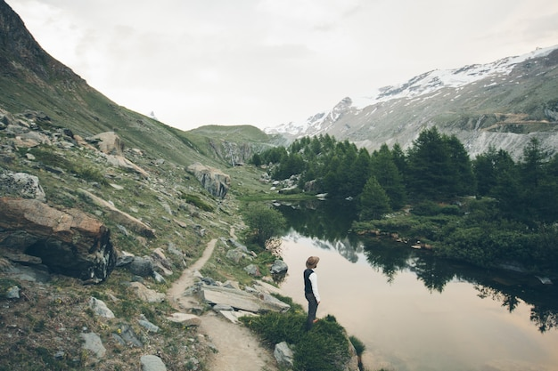 Man with beard wearing trendy clothes in the mountains standing next to the lake