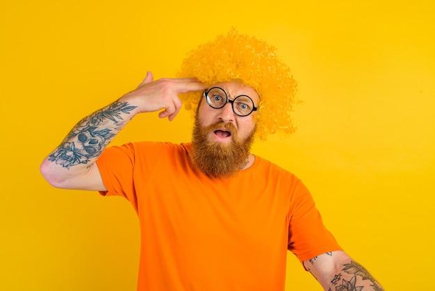 Мужчина с бородой в желтом парике и очках делает жест рукой