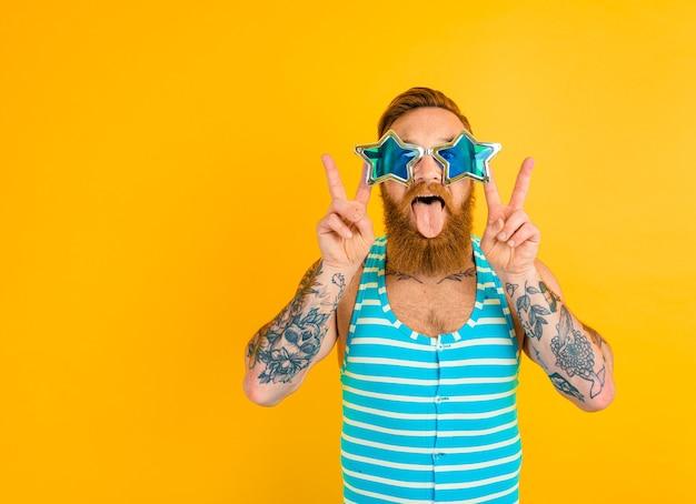 수염 문신과 수영복을 입은 남자는 여름을 준비한다
