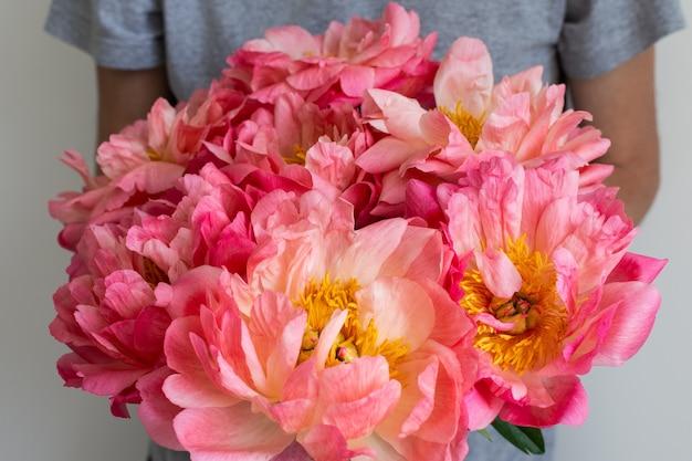 ピンクの牡丹の美しい花束を持つ男