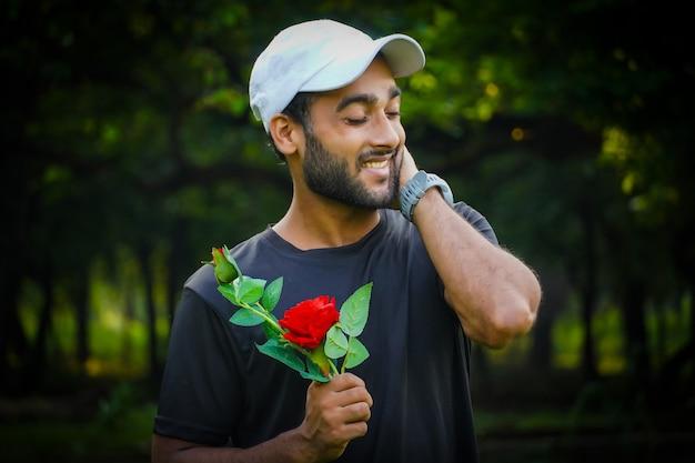 美しい赤いバラの笑顔の恋人の画像を持つ男