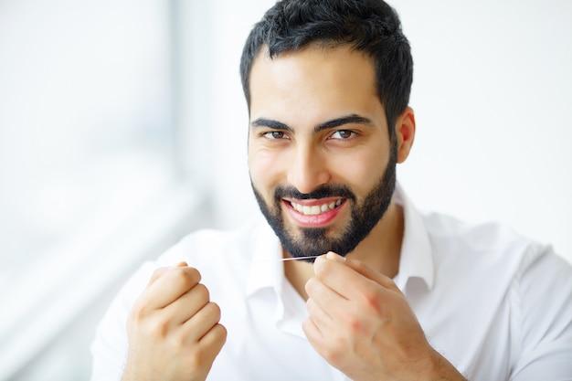Человек с красивой улыбкой чистя здоровые зубы зубной нитью.