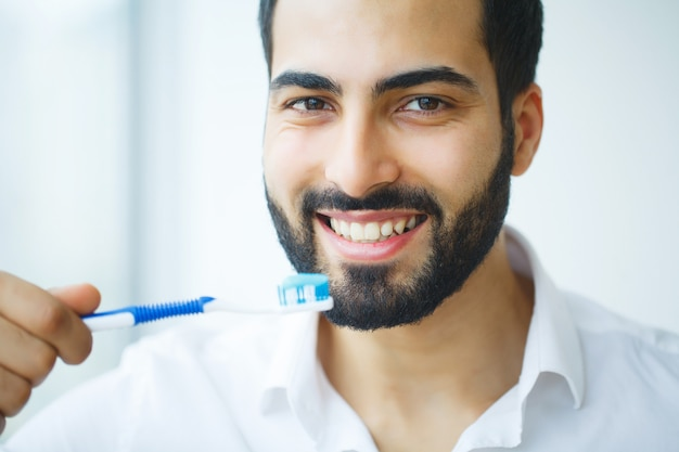 Man with beautiful smile, healthy white teeth with toothbrush.