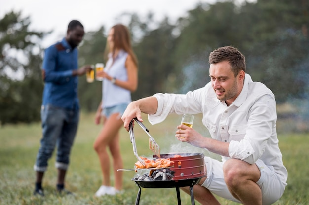 Man with beer attending barbecue for friends