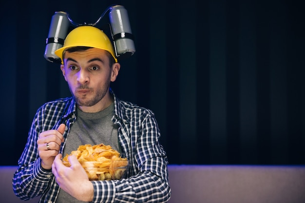 머리에 맥주 헬멧을 가진 남자는 저녁에 소파에 집에 앉아있는 동안 칩을 먹는다.