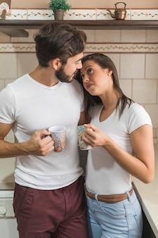 Человек с напитком глядя на подругу в кухне