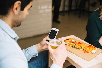 Man with beverage using smartphonein cafe